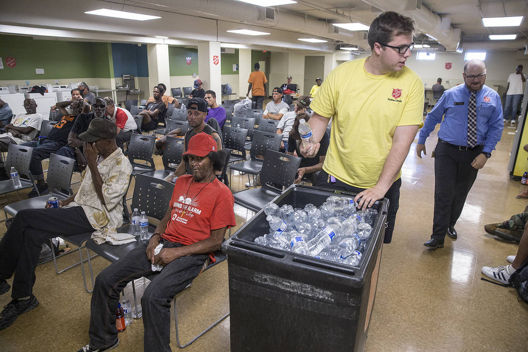 Shelter monitor Boston Brimhall, left, and homeless services coordinator Ryan McDonald hand out water at a cooling station at The Salvation Army on Thursday, July 5, 2018, in Las Vegas. Benjamin H ...