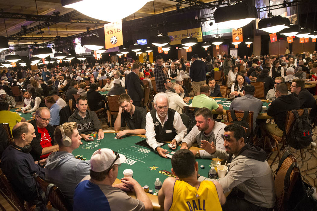 Poker dealer Mark Bowen, center, deals the deck on day one of the main event during the World Series of Poker tournament at the Rio in Las Vegas, Monday, July 2, 2018. Richard Brian Las Vegas Revi ...