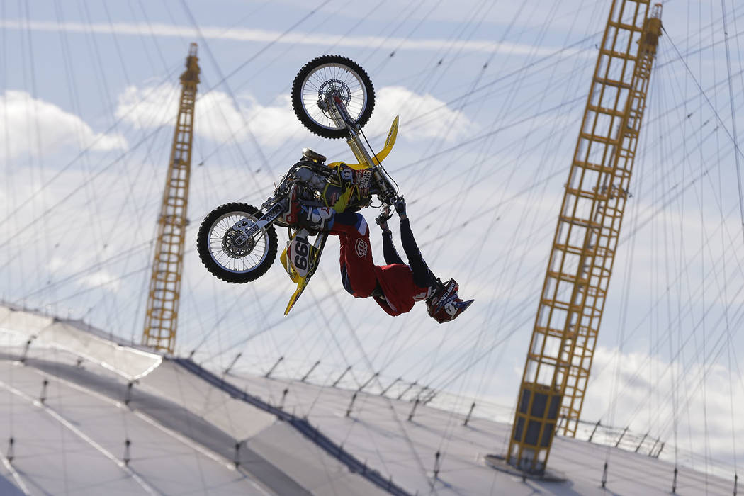 Nitro Circus ringleader and stunt professional Travis Pastrana performs the first motorcycle backflip over the River Thames with a 75-foot wide gap between two floating barges, with the Millennium ...