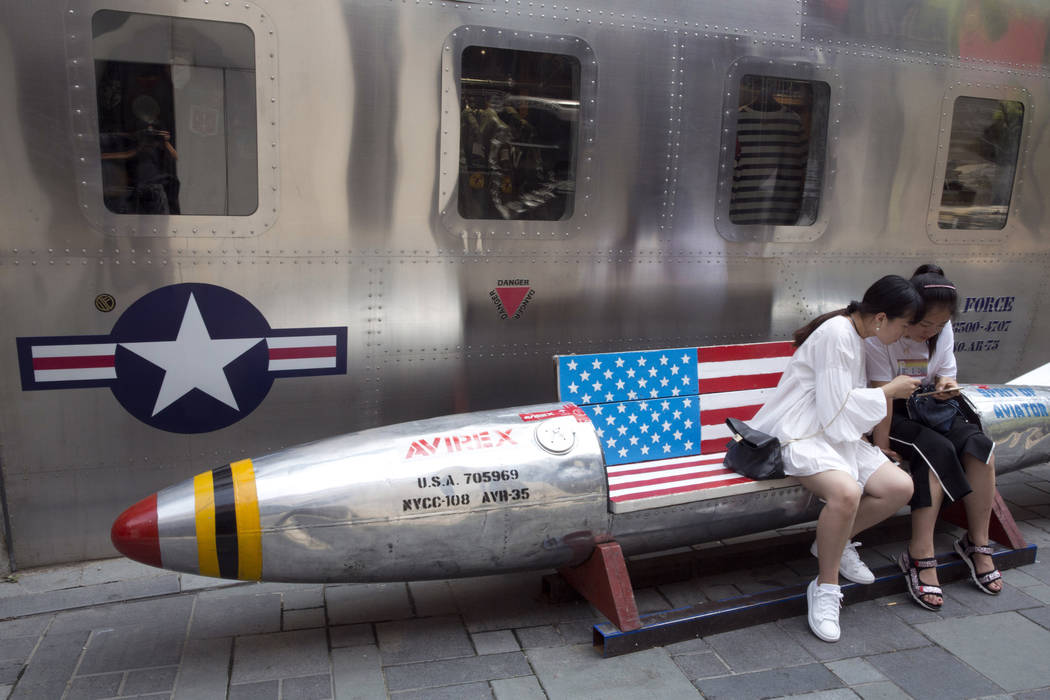 Chinese women look at phone near a rocket-shaped bench with an American flag used as a marketing gimmick for a U.S. apparel shop in Beijing, Friday, July 6, 2018. The United States hiked tariffs o ...