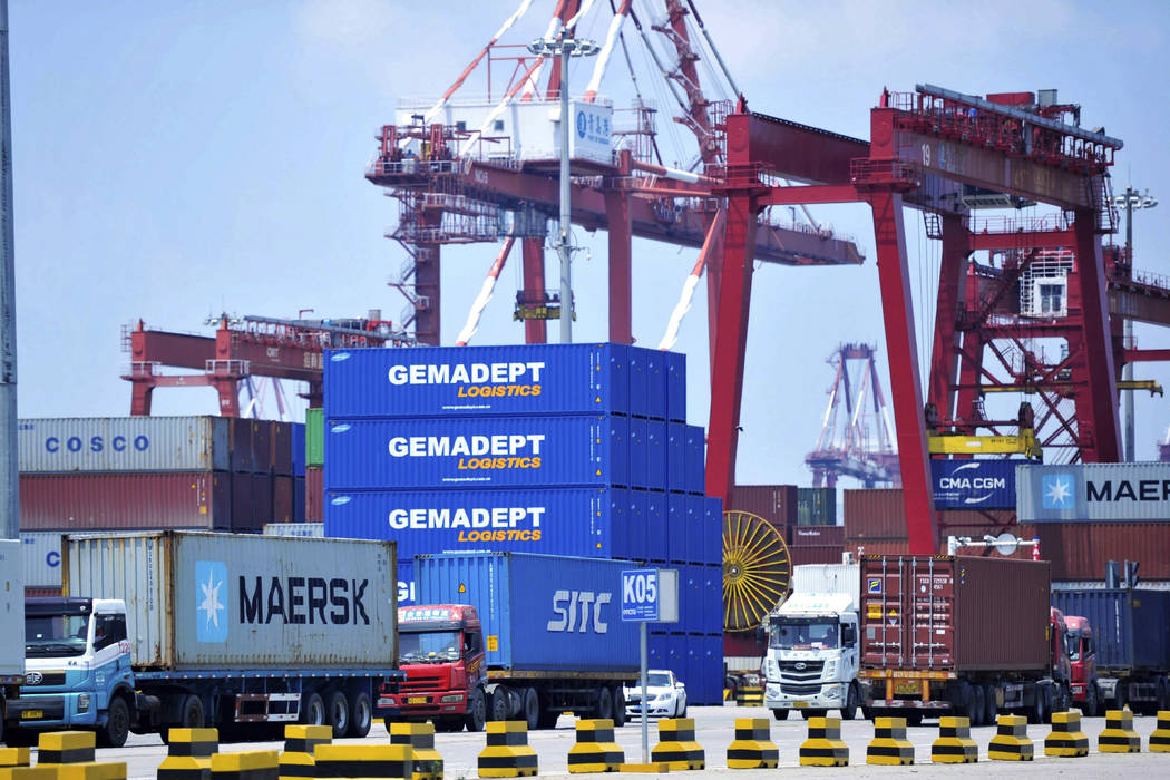 Trucks haul containers from a container port in Qingdao in eastern China's Shandong province Friday, July 6, 2018. The United States hiked tariffs on Chinese imports Friday and Beijing said it imm ...