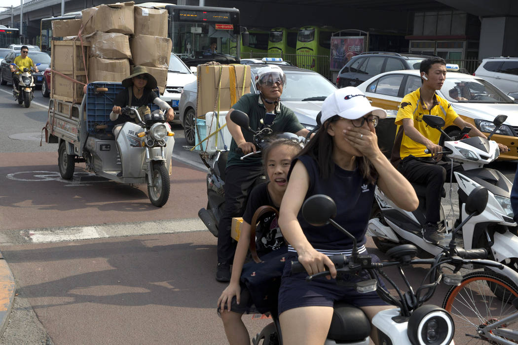 A delivery man transports goods on the streets of Beijing, China, Friday, July 6, 2018. The United States hiked tariffs on Chinese imports Friday and Beijing said it immediately retaliated in a di ...
