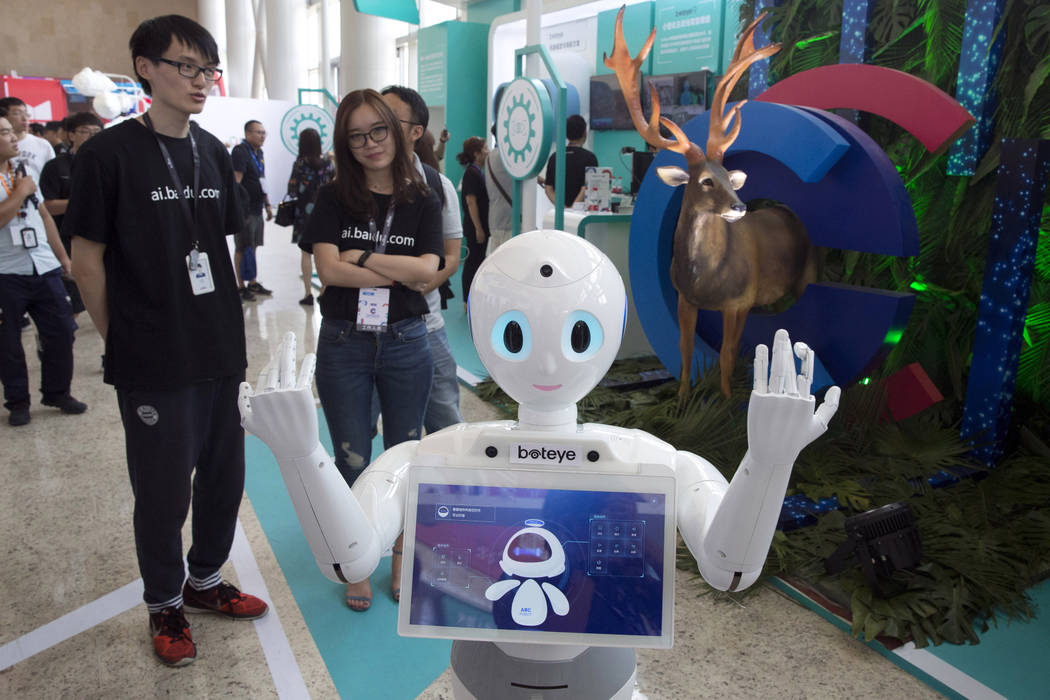 A robot from Chinese search company Baidu welcomes visitors to a developer event in Beijing, July 4, 2018. The Trump administration contends China has deployed predatory tactics in a push to over ...