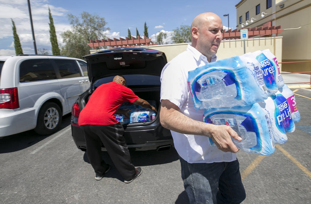 Metro Pizza General Manager Chris Decker, right, receives a water donation from Las Vegas resident Randy Davis during a water bottle drive, Thursday, July 27, 2017, at the pizzeria located at 6720 ...