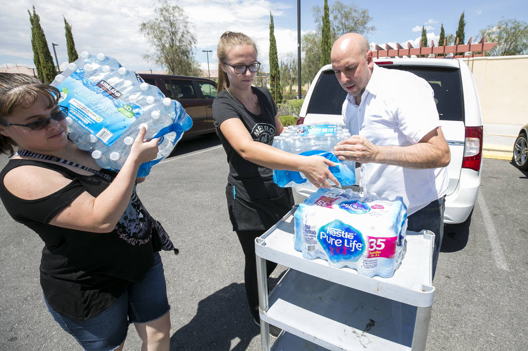 Metro Pizza General Manager Chris Decker, right, and take out host Sydney Butler, center, receive a water donation from Las Vegas resident Elizabeth Backenstow during a water bottle drive, Thursda ...