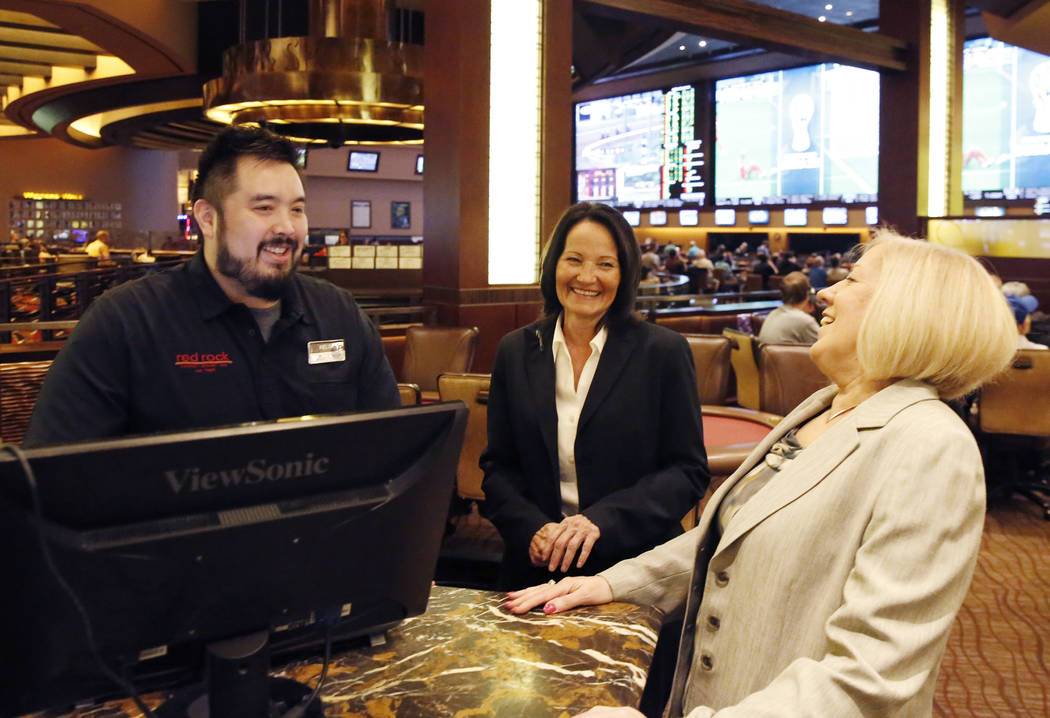 Tracy Mendiola, center, and Kathy Raymond, both poker rooms managers at the Station Casinos, chat with Kelvin Vazquetelles, poker room cashier, at the Red Rock Resort on Tuesday, July 10, 2018, in ...