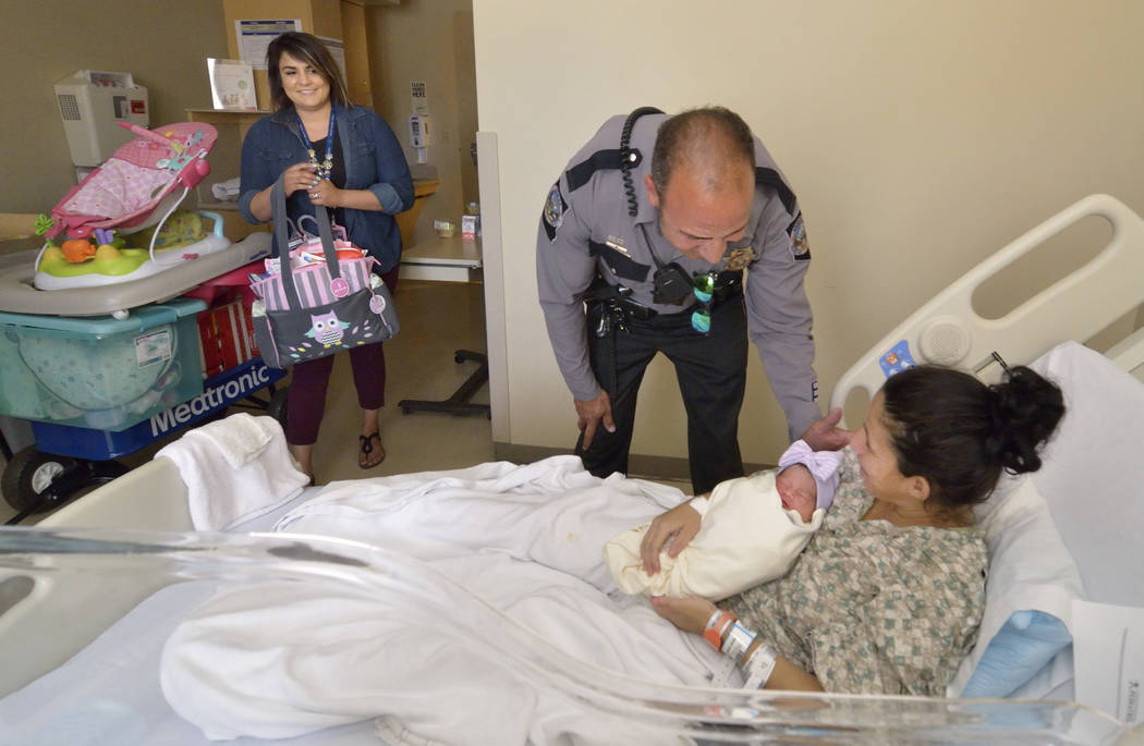 Nevada Highway Patrol dispatch supervisor Jordyn (cq) Albano, left, and trooper Joseph DellaBella deliver gifts to Brenda Valasquez-Cartagena and her daughter Bianca Garcia-Velasquez at Sunrise Ch ...