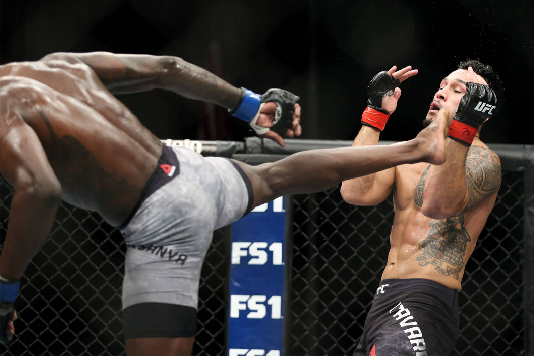 Israel Adesanya, left, connects a kick against Brad Tavares in The Ultimate Fighter 27 Finale middleweight main event bout at the Palms casino-hotel in Las Vegas, Friday, July 6, 2018. Erik Verduz ...