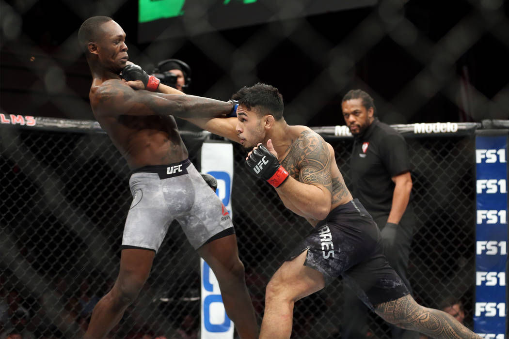 Brad Tavares, right, connects a punch against Israel Adesanya in The Ultimate Fighter 27 Finale middleweight main event bout at the Palms casino-hotel in Las Vegas, Friday, July 6, 2018. Erik Verd ...