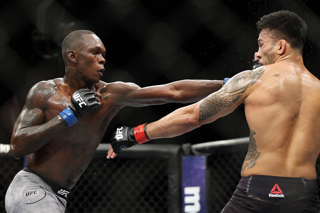 Israel Adesanya, left, connects a punch against Brad Tavares in The Ultimate Fighter 27 Finale middleweight main event bout at the Palms casino-hotel in Las Vegas, Friday, July 6, 2018. Erik Verdu ...