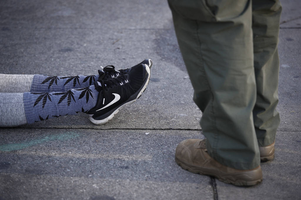 In this March 15, 2018 photo, an undercover Los Angeles County sheriff's deputy stands next to a woman apprehended at an illegal marijuana dispensary in Compton, Calif. (AP Photo/Jae C. Hong)