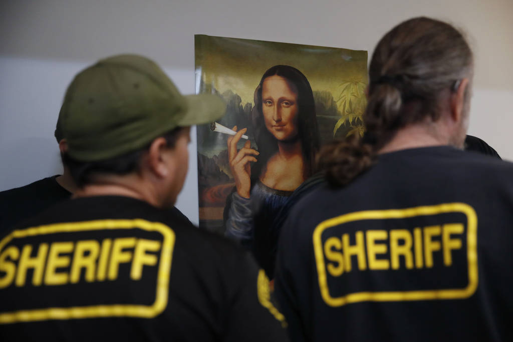 In this March 15, 2018 photo, a group of undercover Los Angeles County sheriff's deputies gather inside an illegal marijuana dispensary during a raid in Compton, Calif. (AP Photo/Jae C. Hong)
