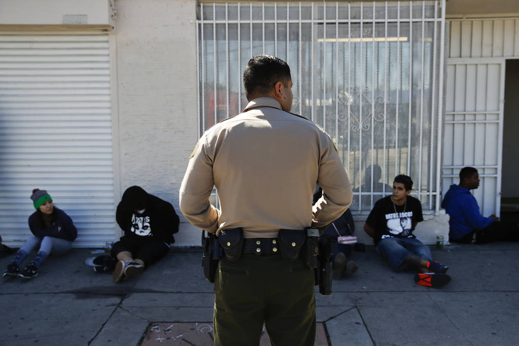 In this March 15, 2018 photo, a Los Angeles County Sheriff's deputy keeps watch on a group of people apprehended at an illegal marijuana dispensary in Compton, Calif. (AP Photo/Jae C. Hong)