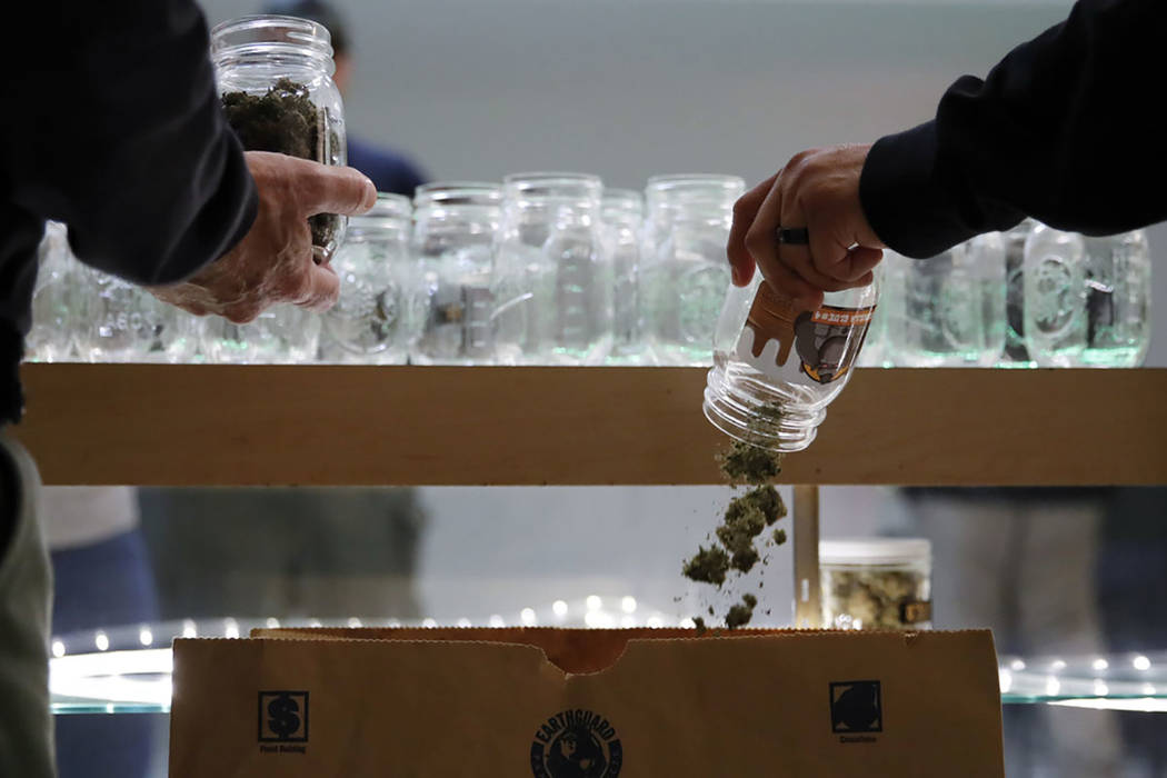 Two undercover Los Angeles County sheriff's deputies dump marijuana into an evidence bag during a raid at an illegal marijuana dispensary during a raid in Compton, Calif. (AP Photo/Jae C. Hong)