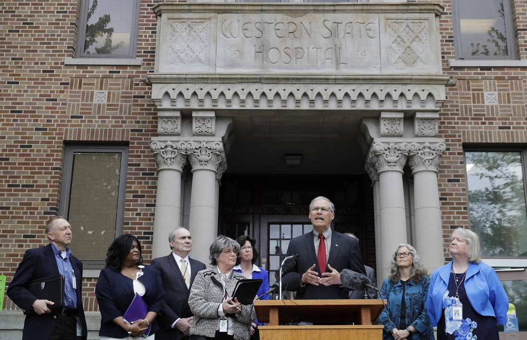 Washington Gov. Jay Inslee, third from right, speaks in front of Western State Hospital in Lakewood, Wash., on May 11, 2018. (AP Photo/Ted S. Warren, File)