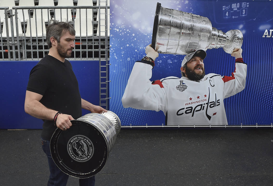 Washington Capitals Alex Ovechkin, from Russia, carries the Stanley Cup trophy at the fan zone in Moscow ahead of the the quarterfinal match between Russia and Croatia at the 2018 soccer World Cup ...