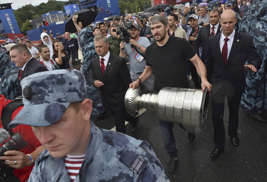 Washington Capitals Alex Ovechkin, from Russia, holds the Stanley Cup trophy at the fan zone in Moscow ahead of the the quarterfinal match between Russia and Croatia at the 2018 soccer World Cup t ...