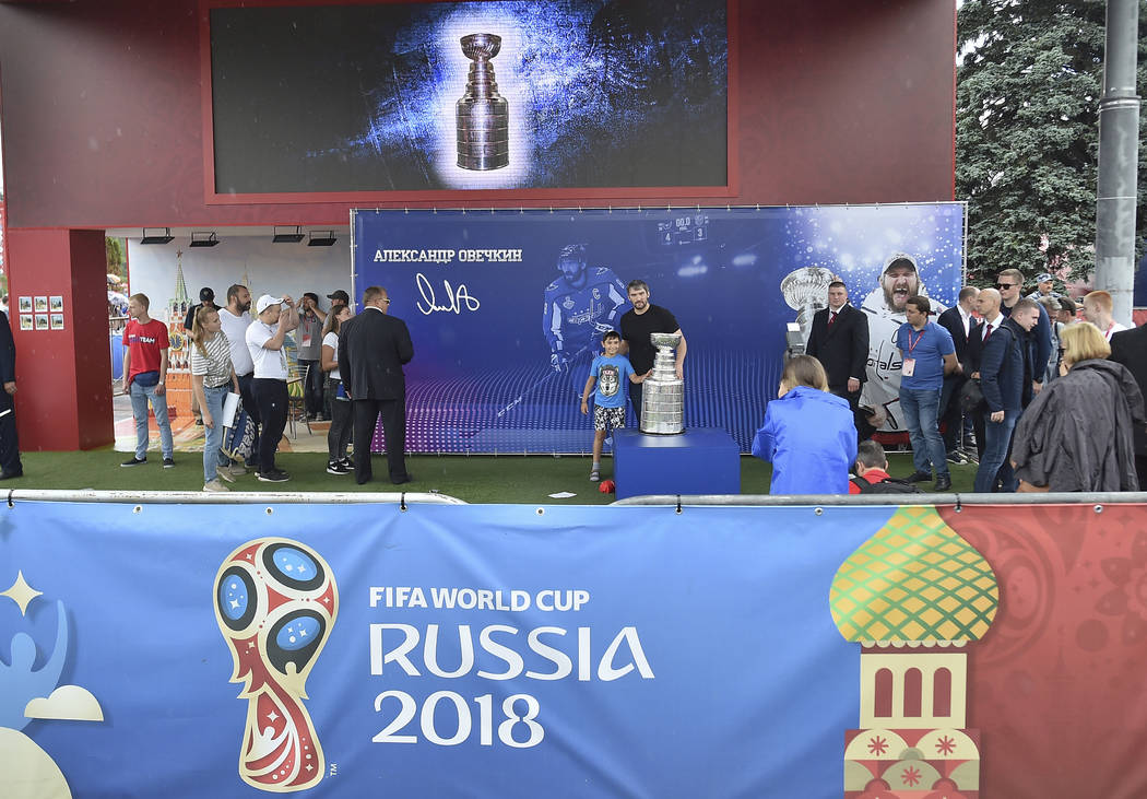 Washington Capitals Alex Ovechkin, from Russia, center, poses with the Stanley Cup trophy in the fan zone in Moscow ahead of the the quarterfinal match between Russia and Croatia at the 2018 socce ...