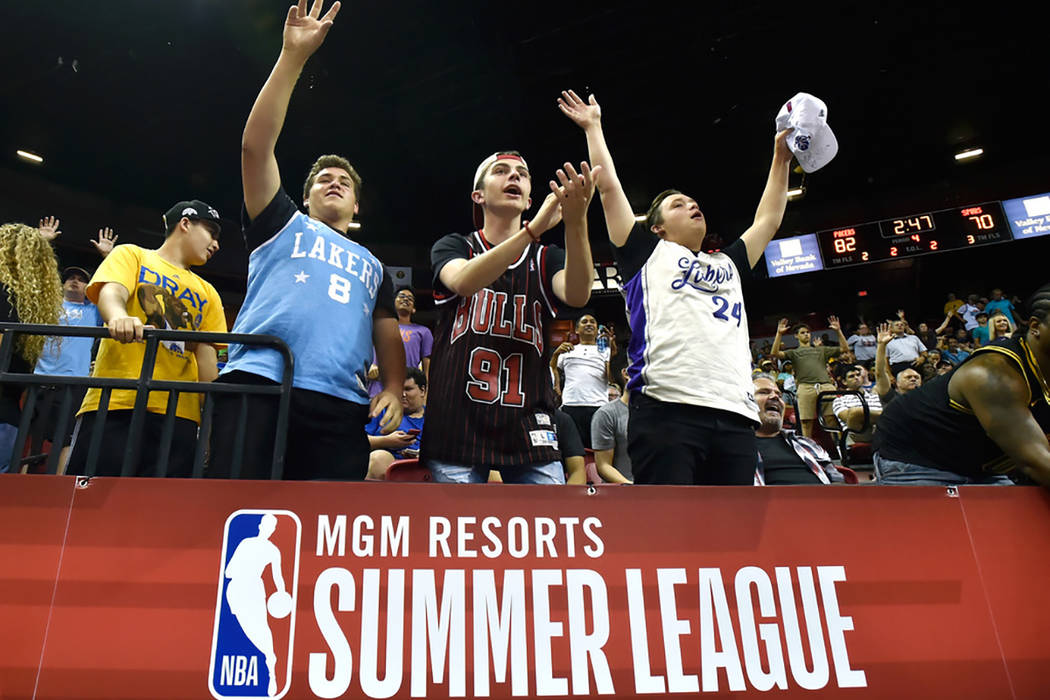 Basketball fans from left, Ayden Matheny, Bill Smith and Chase Matheny cheer during an NBA summer league basketball game between the San Antonio Spurs and Indiana Pacers Saturday, July 7, 2018, in ...