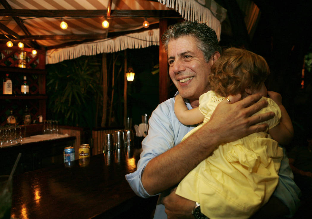 Chef Anthony Bourdain holds his daughter Ariane in Miami Beach on Nov. 12, 2008. (AP Photo/Lynne Sladky, File)