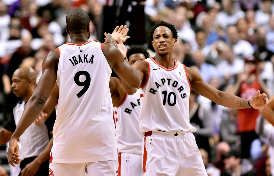 Nathan Denette/The Canadian Press via AP Toronto Raptors guard DeMar DeRozan (10) celebrates with teammate Serge Ibaka (9) after a basket against the Washington Wizards on Tuesday in Toronto. (Nat ...