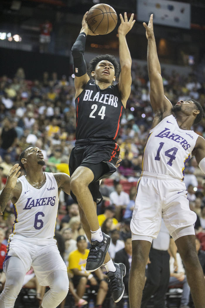 Portland Trail Blazers guard Anfernee Simons (24) drives past Los Angeles Lakers defenders Xavier Rathan-Mayes (6) and Malik Newman (14) in the second quarter during the NBA Summer League finals o ...