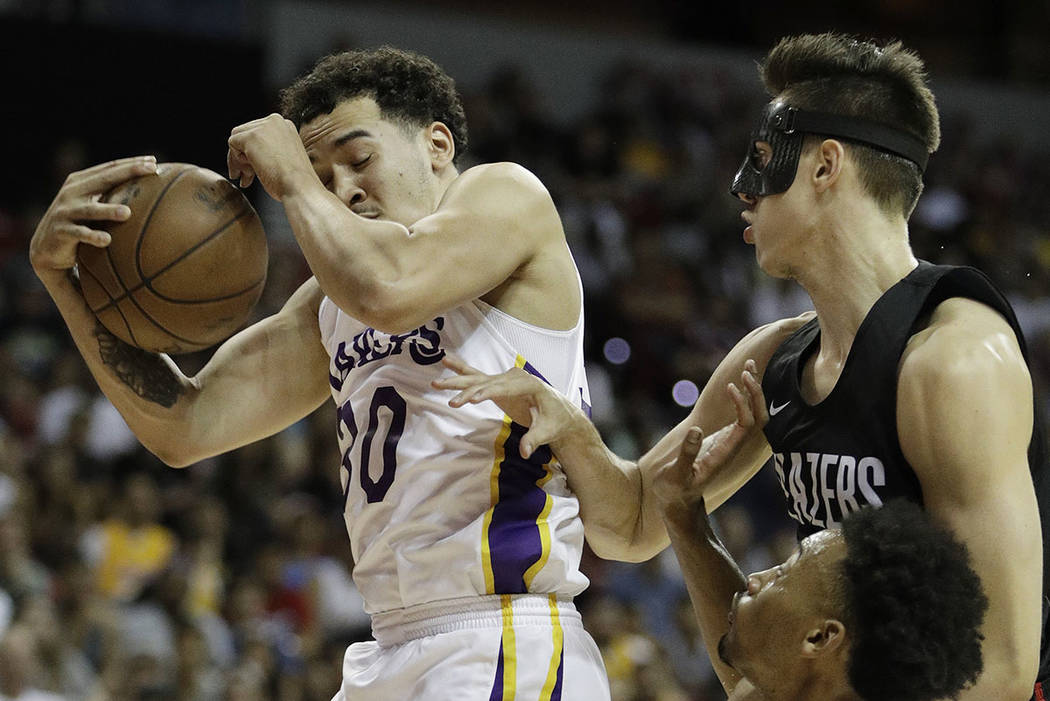 Portland Trail Blazers' Zach Collins, right, fouls Los Angeles Lakers' Jeffrey Carroll during the first half of an NBA summer league basketball game Tuesday, July 17, 2018, in Las Vegas. (AP Photo ...