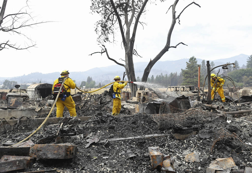 Lake Forest volunteer firefighters from left, Kyle Potter, Dylan Beck and Jerod Ellis work on putting out hot spots in an area burned down by the Klamathon Fire Friday, July 6, 2018, in Hornbrook, ...