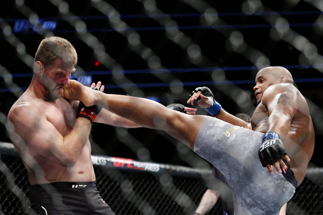 Daniel Cormier, right, lands a kick against Stipe Miocic in the first round of the heavyweight title bout during UFC 226 at T-Mobile Arena in Las Vegas, Saturday, July 7, 2018. Erik Verduzco Las V ...