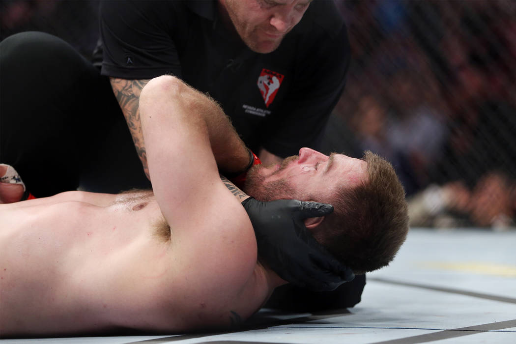 Stipe Miocic gets assistance after getting knocked out by Daniel Cormier in the heavyweight title bout during UFC 226 at T-Mobile Arena in Las Vegas, Saturday, July 7, 2018. Cormier won by way of ...