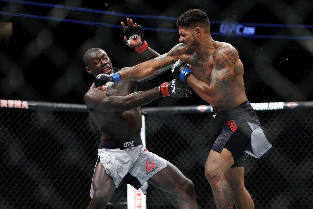 Curtis Millender, left, takes a punch against Max Griffin in the welterweight bout during UFC 226 at T-Mobile Arena in Las Vegas, Saturday, July 7, 2018. Millender won by unanimous decision. Erik ...