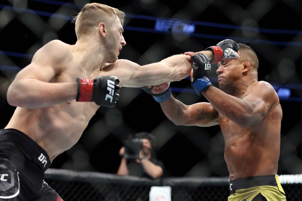 Dan Hooker, left, connects a punch against Gilbert Burns in the lightweight bout during UFC 226 at T-Mobile Arena in Las Vegas, Saturday, July 7, 2018. Hooker won by way of knockout in the first r ...