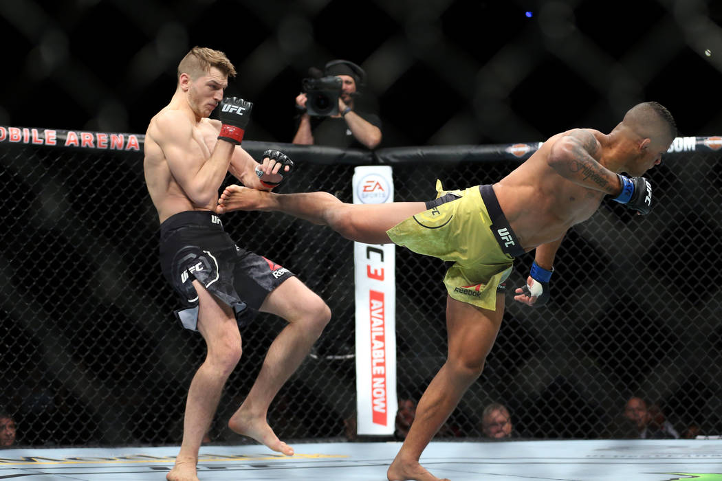 Dan Hooker, left, takes a kick against Gilbert Burns in the lightweight bout during UFC 226 at T-Mobile Arena in Las Vegas, Saturday, July 7, 2018. Hooker won by way of knockout in the first round ...