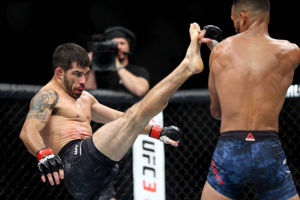 Raphael Assuncao, left, throws a kick against Rob Font in the bantamweight bout during UFC 226 at T-Mobile Arena in Las Vegas, Saturday, July 7, 2018. Assuncao won by unanimous decision. Erik Verd ...