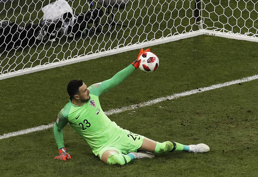 Croatia goalkeeper Danijel Subasic stops a shot from Russia's Fyodor Smolov during a penalty shootout at the end of the quarterfinal match between Russia and Croatia at the 2018 soccer World Cup a ...