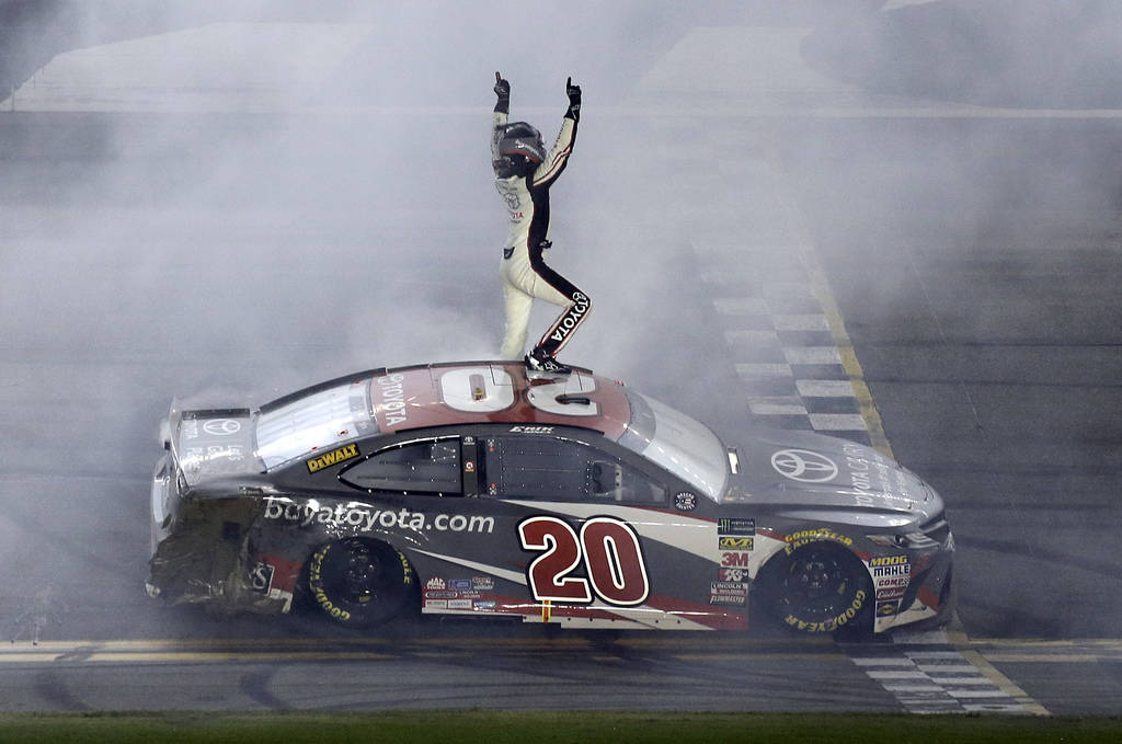 Erik Jones celebrates in front of fans after winning the NASCAR Cup Series auto race at Daytona International Speedway, Saturday, July 7, 2018, in Daytona Beach, Fla. (AP Photo/Terry Renna)