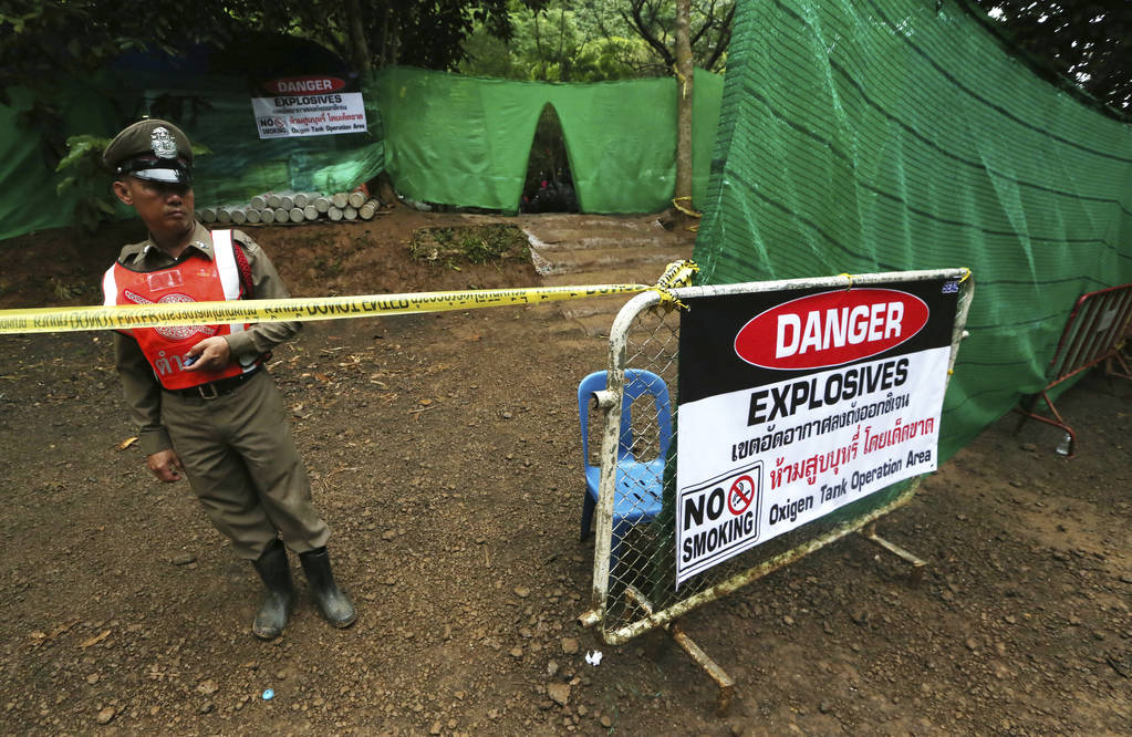 Thai police stand guard near a cave where 12 boys and their soccer coach have been trapped since June 23, in Mae Sai, Chiang Rai province, in northern Thailand Sunday, July 8, 2018. (AP Photo/Sakc ...