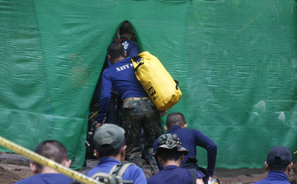 Rescuer arrive near cave where 12 boys and their soccer coach have been trapped since June 23, in Mae Sai, Chiang Rai province, in northern Thailand Sunday, July 8, 2018. (AP Photo/Sakchai Lalit)