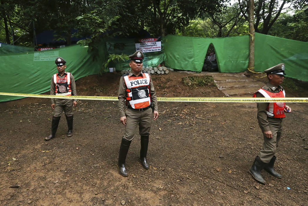 Thai policemen stand guard near a cave where 12 boys and their soccer coach have been trapped since June 23, in Mae Sai, Chiang Rai province, in northern Thailand Sunday, July 8, 2018. (AP Photo/S ...
