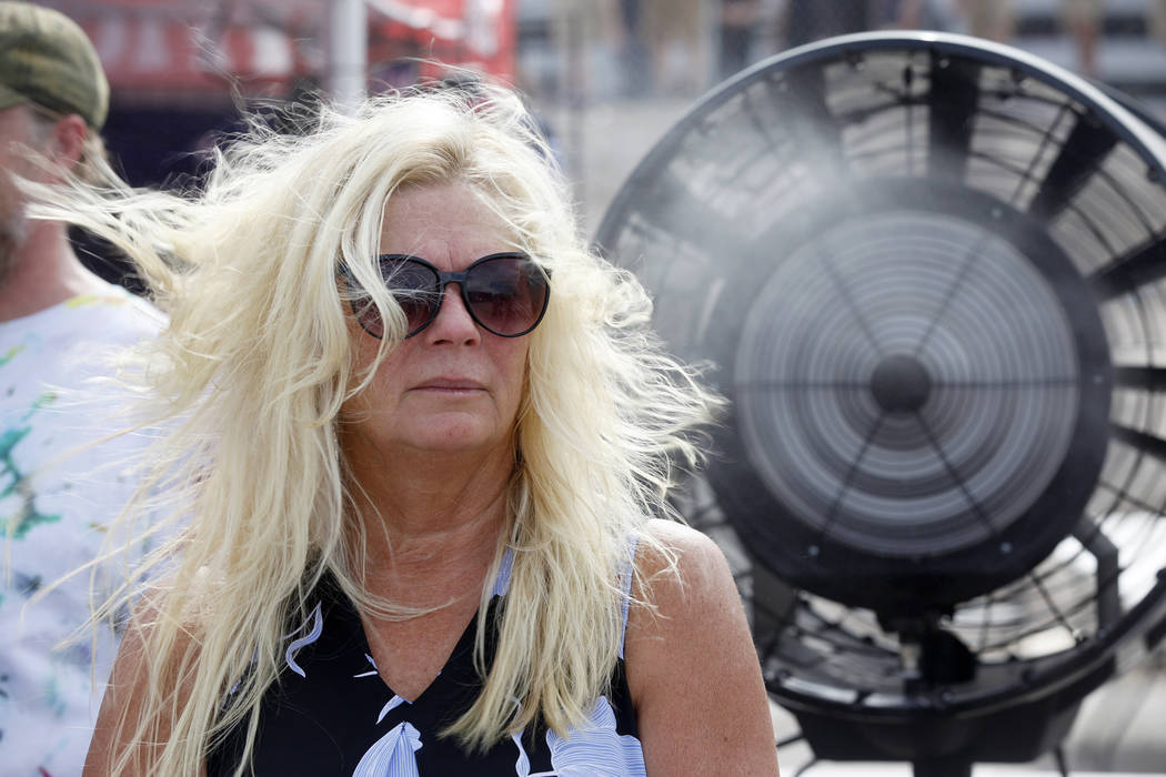 Janet Pleasants cools down in front of a giant fan at Evel Live, an event where Travis Pastrana attempted to exceed three of Evel Knievel's famous jumps in a lot behind Planet Hollywood hotel-reso ...