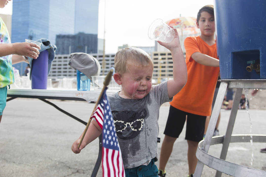 Oliver Tuck, 2, pours water on his head to cool down at the Evel Live event where Travis Pastrana attempted to exceed three of Evel Knievel's famous jumps in a lot behind Planet Hollywood hotel-re ...