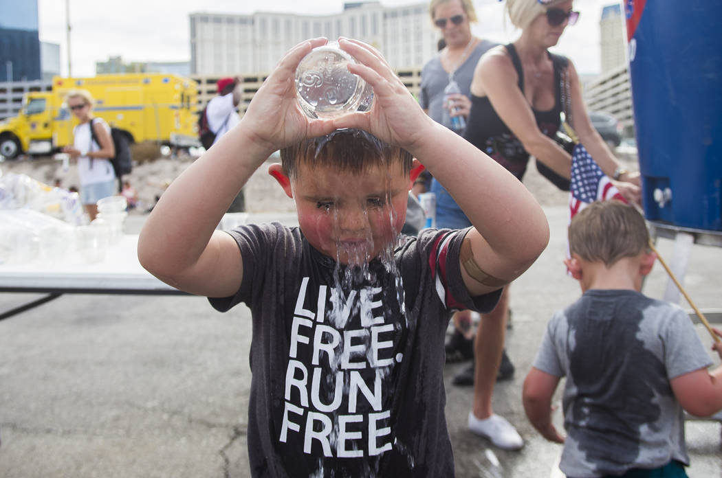 Sawyer Tuck, 4, pours water on his head to cool down at the Evel Live event where Travis Pastrana attempted to exceed three of Evel Knievel's famous jumps in a lot behind Planet Hollywood hotel-re ...