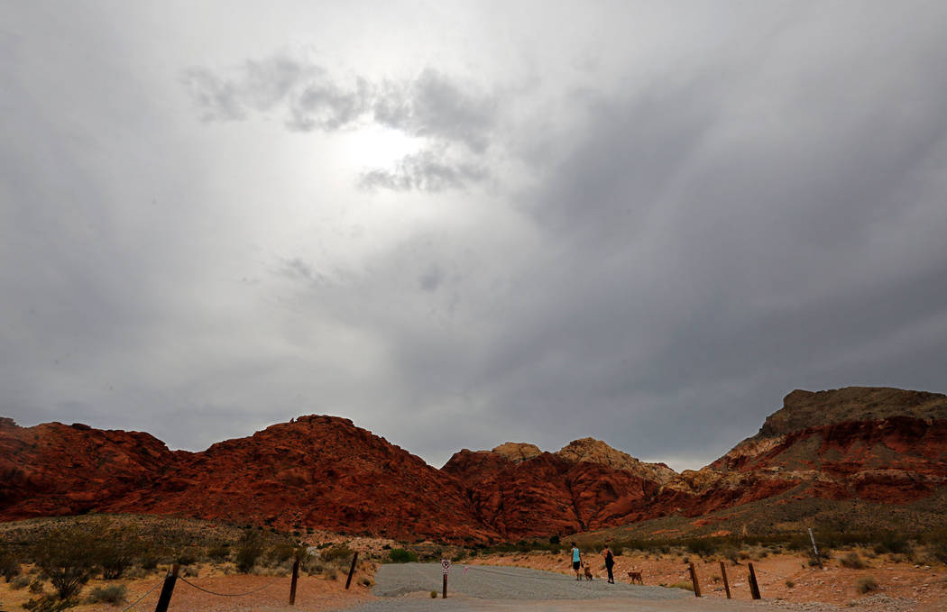 Cloudy sky is seen at Red Rock Canyon in Las Vegas, Sunday, July 8, 2018, while a couple walks with their dogs. Chitose Suzuki Las Vegas Review-Journal @chitosephoto