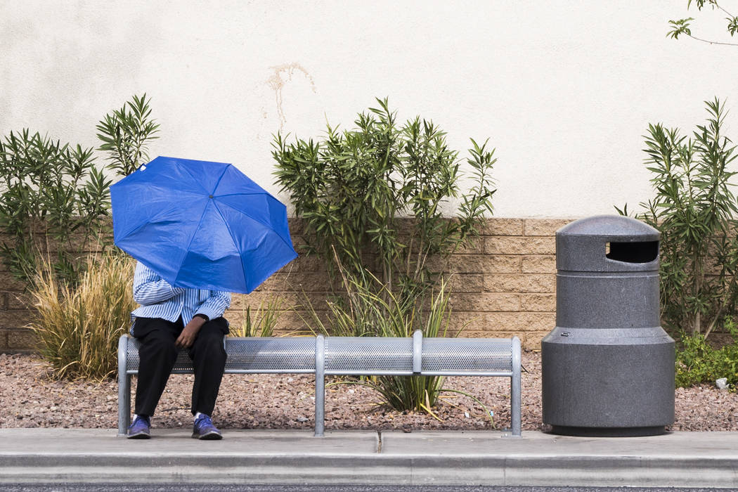 In triple-digit temperatures, a woman waits for the bus near University Road and Maryland Parkway in Las Vegas, Sunday, July 8, 2018. (Marcus Villagran/Las Vegas Review-Journal) @brokejournalist