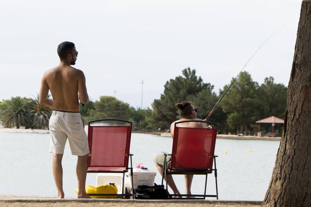 In triple-digit temperatures, two men fish at the lake at Sunset Park in Las Vegas, Sunday, July 8, 2018. (Marcus Villagran/Las Vegas Review-Journal) @brokejournalist