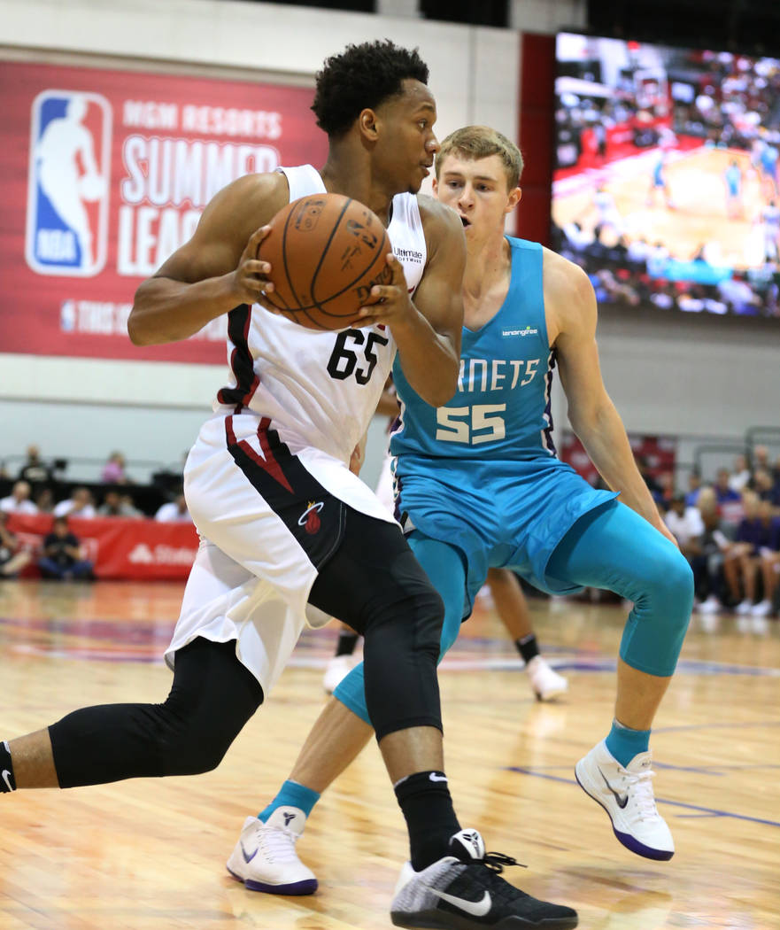 The Miami Heat guard Rashad Vaughn (65) drives past the Charlotte Hornets' guard J.P. Macura during an NBA summer league basketball game at the Cox Pavilion on Sunday, July, 2018, in Las Vegas. Bi ...