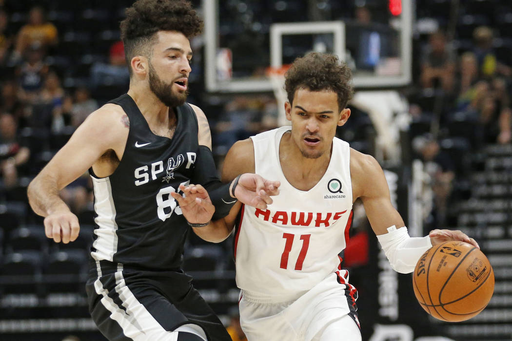 Atlanta Hawks guard Trae Young (11) drives around San Antonio Spurs guard London Perrantes, left, during the first half of an NBA summer league basketball game Tuesday, July 3, 2018, in Salt Lake ...