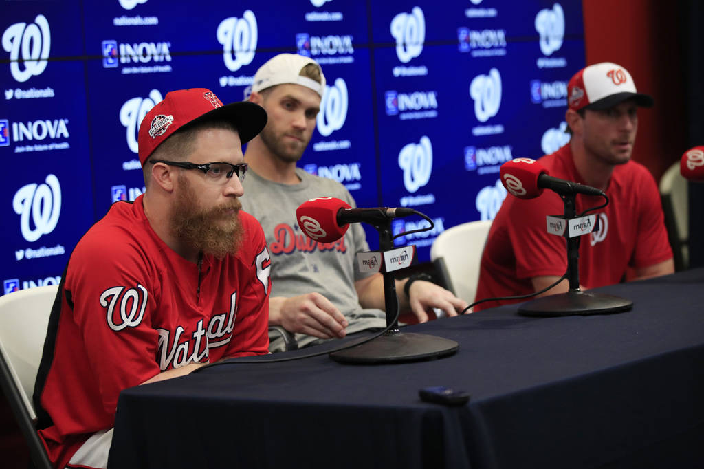 From left to right, Washington Nationals pitcher Sean Doolittle, right fielder Bryce Harper and pitcher Max Scherzer speak to reporters during a news conference at Nationals Park in Washington, Su ...