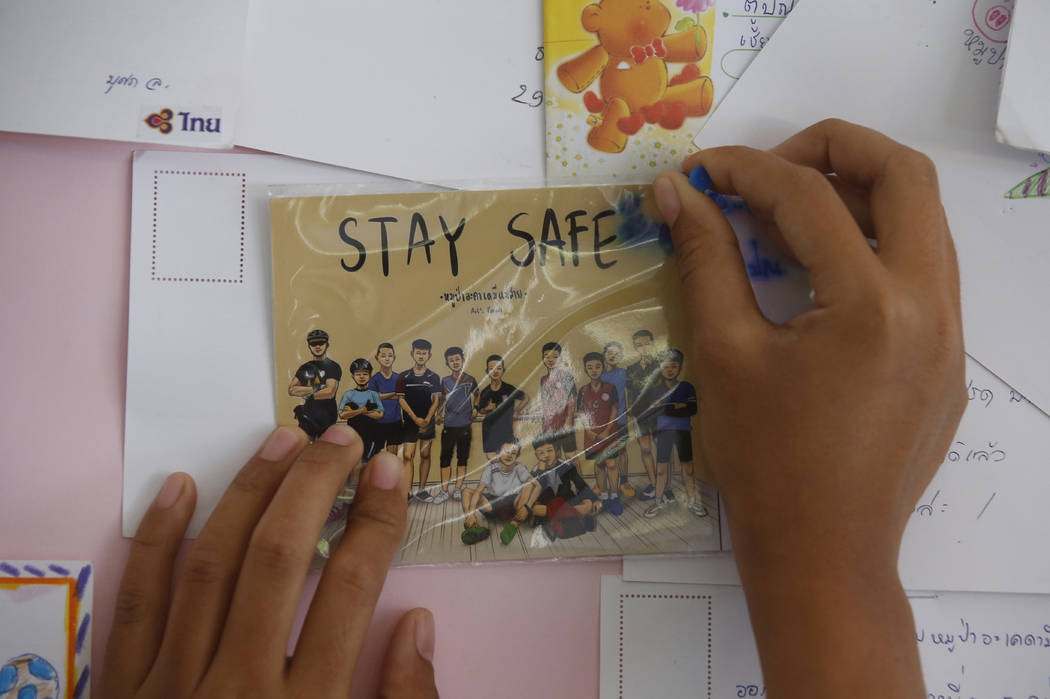 A Thai well wisher puts a poster to pray for boys and their soccer coach who have been trapped since June 23, in Mae Sai, Chiang Rai province, northern Thailand Monday, July 9, 2018. Expert divers ...