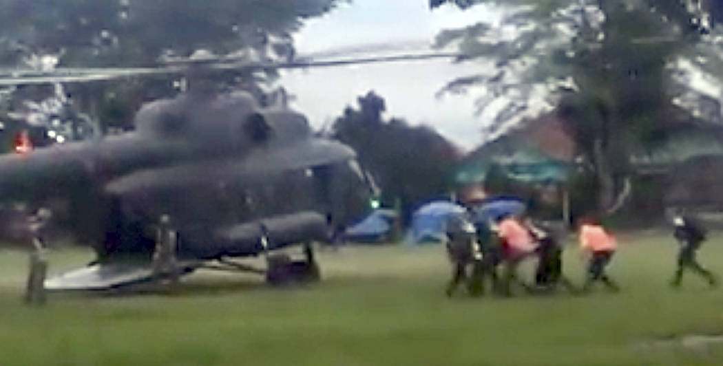 In this image made from video taken Sunday, July 8, 2018, an emergency team carries a stretcher believed to be carrying one of the rescued boys from the flooded cave to a waiting helicopter in Mae ...